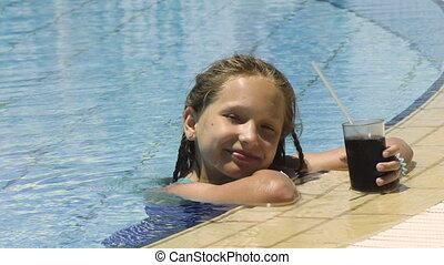 Little girl in swimming pool with cold drink