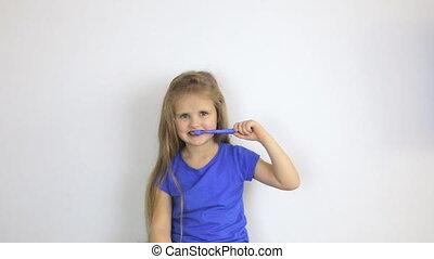 Little girl in t-shirt brushes teeth - Little girl in blue t...