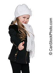 Little girl in the black coat holds her thumb up