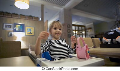 Little girl in the cafe, she sits on a children's chair. Whose hand is that it entertains with a napkin.