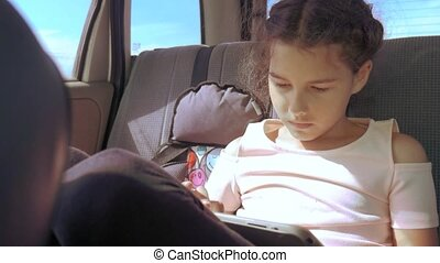 Little girl in the car with a tablet goes on a trip to America lifestyle Texas. girl in car concept travel transport