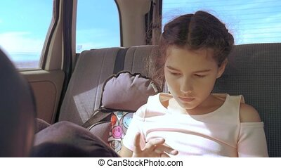 Little girl in the car with a tablet goes on a trip to America Texas. girl in car concept lifestyle travel transport