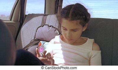 Little girl in the car with a tablet goes on a trip to America Texas. girl in car concept travel lifestyle transport