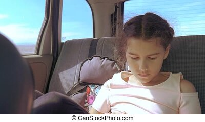 Little girl in the car with a tablet goes on a trip to America Texas. girl in car lifestyle concept travel transport