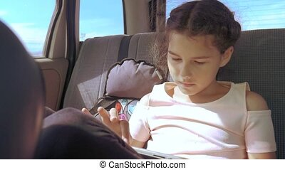 Little girl in the car with a tablet goes on a trip to America Texas. girl lifestyle in car concept travel transport