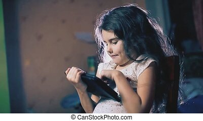 little girl in the evening reads social media posts on a tablet in the room indoors. children and lifestyle internet concept