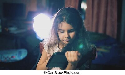 little girl in the evening reads social media posts on a tablet in the room indoors. children and internet concept lifestyle