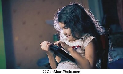 little girl in the evening reads social media posts on a...