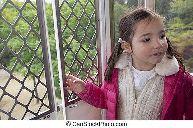 Little girl in the ferris wheel cabin