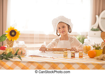 little girl in the form of a cook rolls out the dough in the kitchen