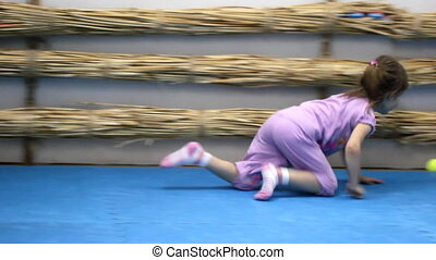 Little girl in the gym playing tenn