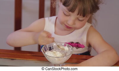 Little girl in the kitchen at home chatting and eating ice cream. Cute little girl laughsing and eating ice cream in a bowl in the kitchen. Close up shot