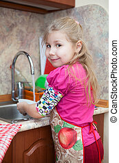 Little girl in the kitchen washing dishes