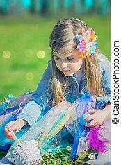 Little girl in the park, holding easter egg and basket