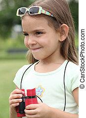 little girl in the park looking through binoculars