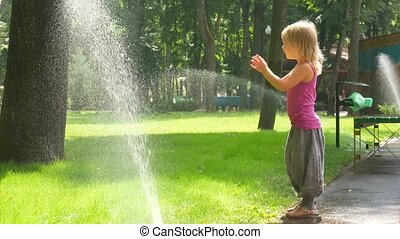 Little girl in the park under the drops of watering pad