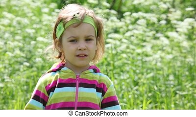 Little girl in the purple blouse on the green field goes to the camera