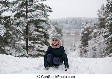 Little girl in the winter snowy Park.