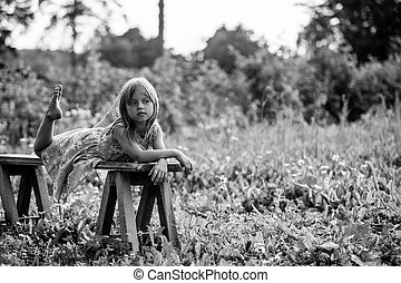 Little girl in the yard of a country house. Black and white photo.