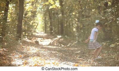 Little girl in the yellow autumn forest. Beautiful sunlight....