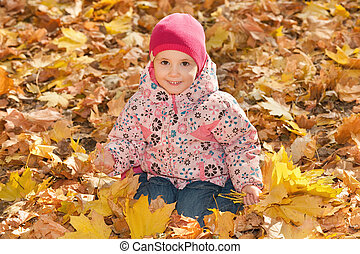 Little girl in the yellow leaves