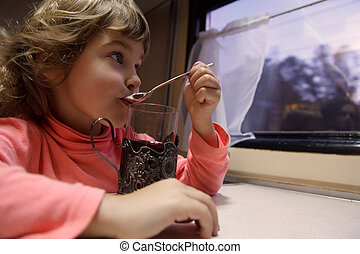 Little girl in train car. Drinks tea from glass and looks out of window.
