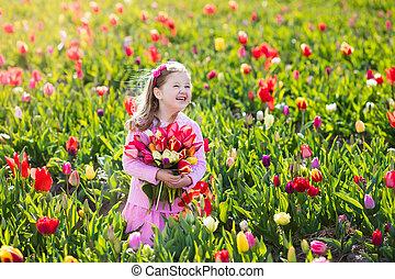 Little girl in tulip flower garden