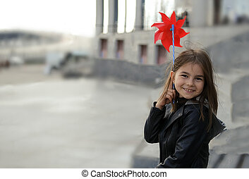 Little girl in urban surroundings with red wind spinner