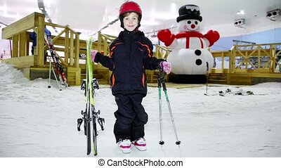 Little girl in warm clothes and helmet stands with skis