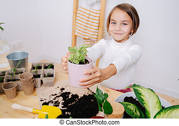 Little girl in warm clothes showing seedlings in pot, that she replanted herself