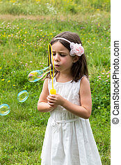 Little girl in white dress blowing bubbles at the park