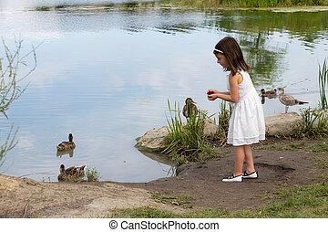 Little girl in white dress feeding ducks at the pond