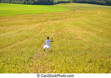 Little girl in white dress in afternoon run field