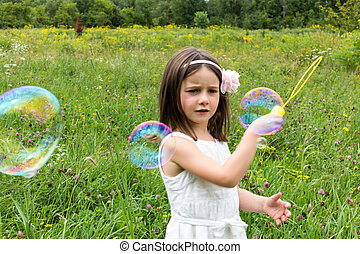 Little girl in white dress playing with bubble maker in the park