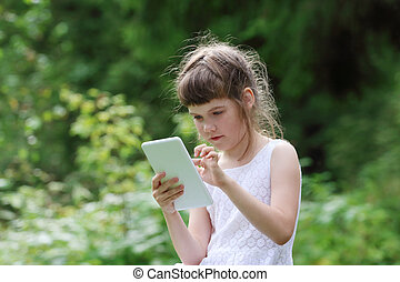 Little girl in white dress plays with tablet pc in green park at summer day