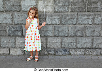 Little girl in  white sarafan eats an ice-cream and holds an air marble near  stone wall