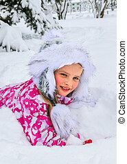 Little girl in winter clothes under snow fir-tree.