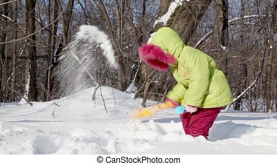 Little girl in winter coat snow shovel digs and throws it up