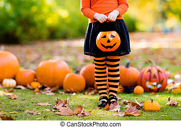 Little girl in witch costume on Halloween trick or treat -...