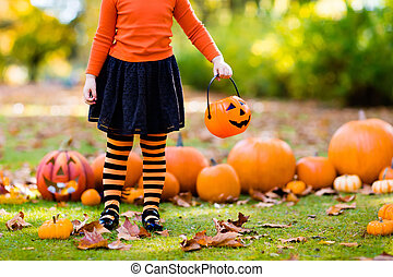 Little girl in witch costume on Halloween trick or treat - ...