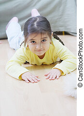 Little girl in yellow laying on floor