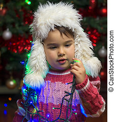 Little girl indoor on christmas day playing with tree lights