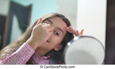 little girl indoors schoolgirl smears face cream. face care...