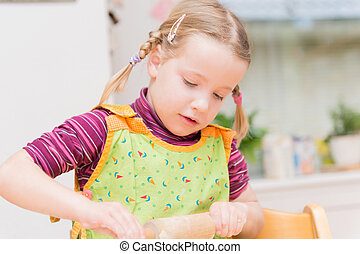 Little girl is baking some cookies in the kitchen