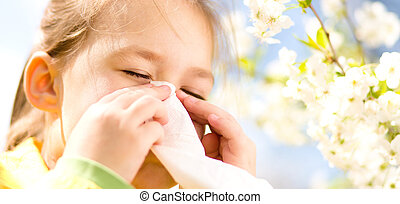 Little girl is blowing her nose