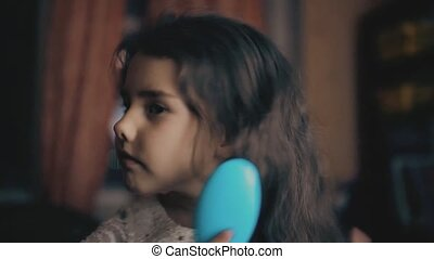 little girl is brushing her hair in the evening in the room...