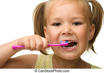 Little girl is cleaning teeth using toothbrush
