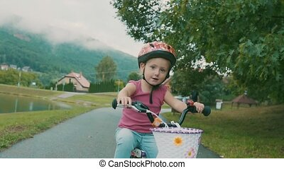 Little girl is cycling in the nature by the lake. - Cute...