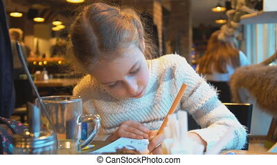 Little girl is drawing in a cafe.