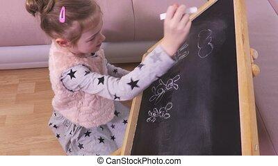 Little girl is drawing on a blackboard